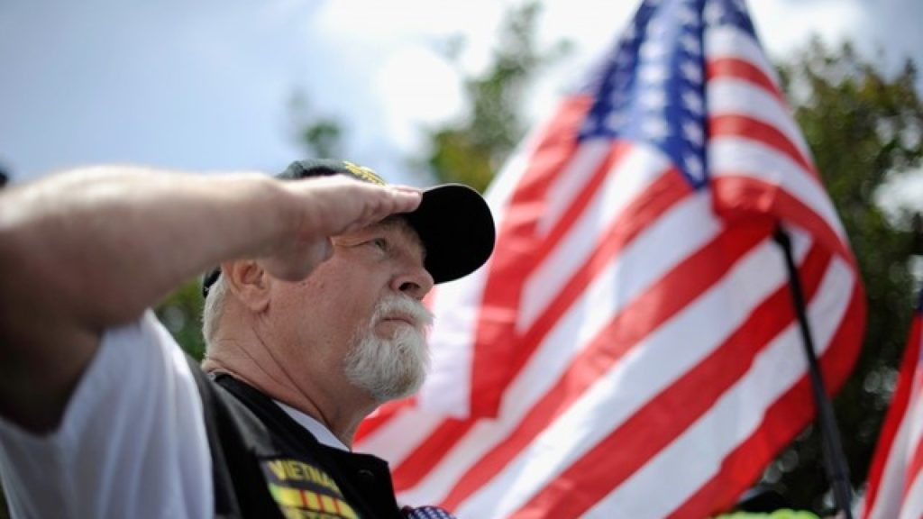 veteran saluting with flag in background