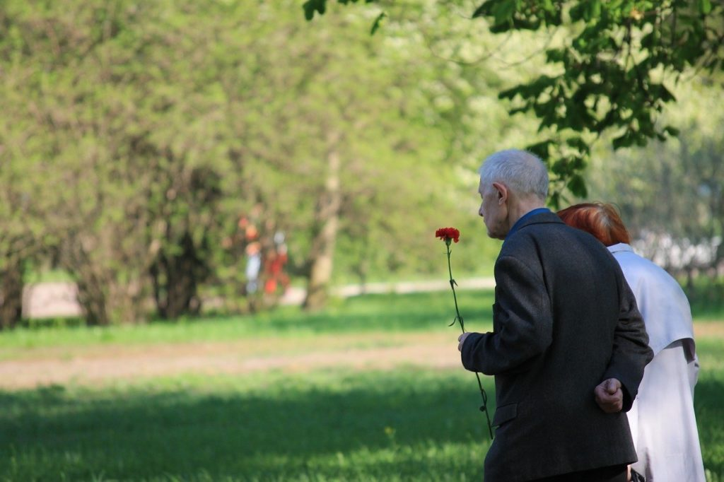 man and woman walking with flower