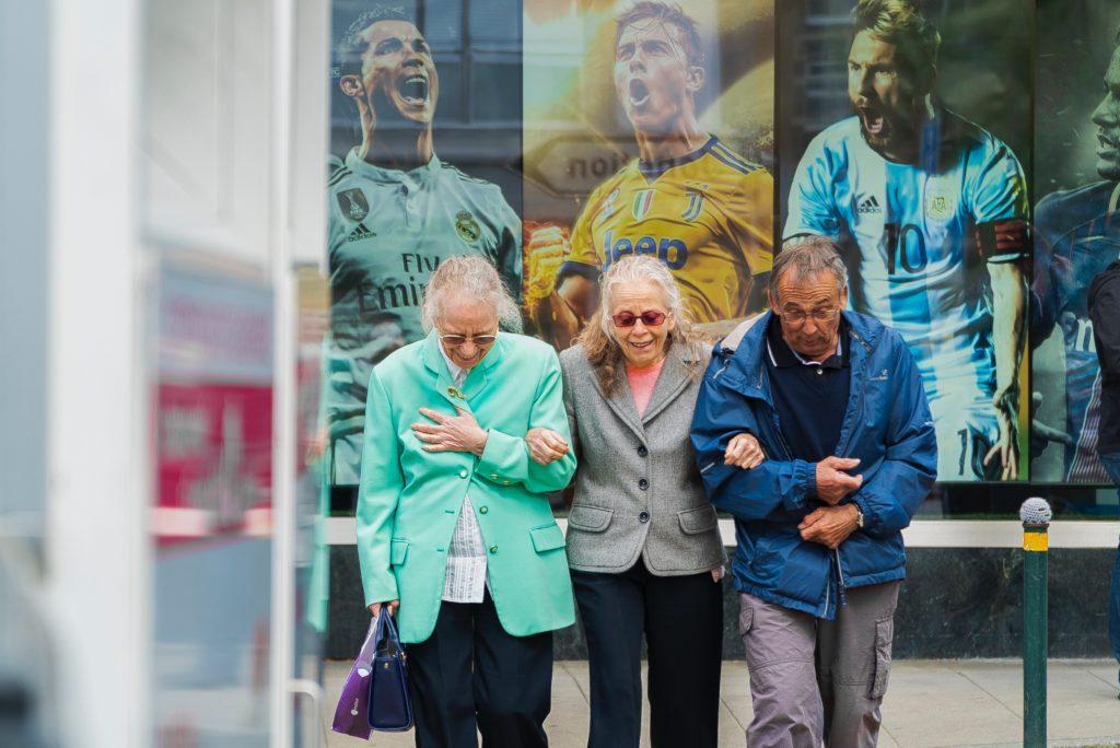 three elderly people walking arm in arm